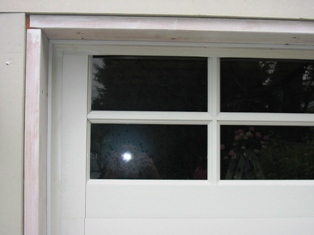 Notice how the top four inches of the door is ABOVE the DOOR OPENING. Custom Garage Doors or REAL Carriage Doors will solve this ugly situation for your carriage house garage doors.  Other opening styles for Custom Garage Doors or Carriage Doors include:  Out-Swing, In Swing, Hinged, Swinging, Slide, or Fold.  The  choice is yours for a carriage house door, custom garage doors, or real carriage doors!