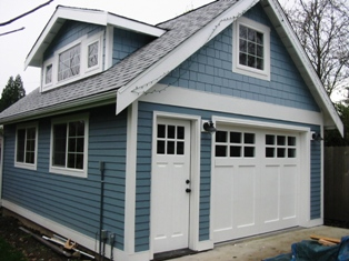 Custom swing carriage doors for a carriage door garage.  Made with a corresponding entry door.  Note the symetrical alignment of all craftsman style door elements.