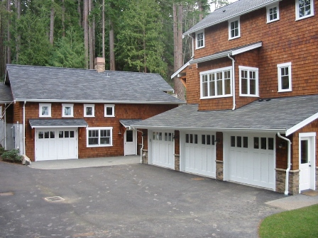 Four Seattle Garage Doors.  A Swing Carriage Door, or hinged carraige door, for the real carriage door garage on the left.  Three custom carriage style garage doors for the vintage garage on the right.