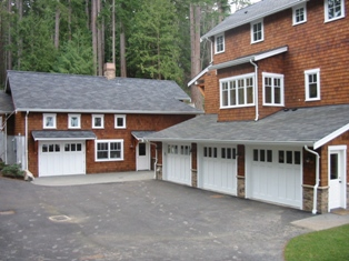 Four Custom Carriage House Garage Doors.  A Swing Carriage Door, or hinged carraige door, for the real carriage door garage on the left.  Three custom carriage style garage doors for the vintage garage on the right.